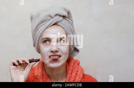 Young beautiful girl cleaning her teeth in bathroom, with natural homemade ecological mask on her face. Beauty, skin care, health care concept. Place - Stock Photo