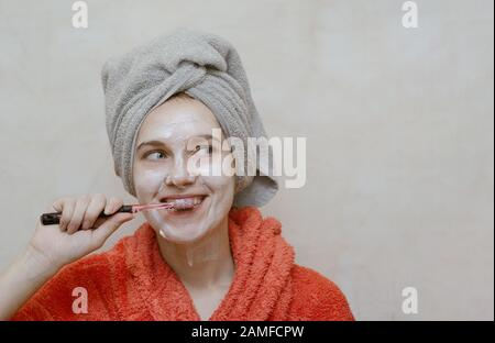 Young beautiful smiling girl cleaning her teeth in bathroom, with natural homemade ecological mask on her face. Skin care, health care and beauty conc - Stock Photo