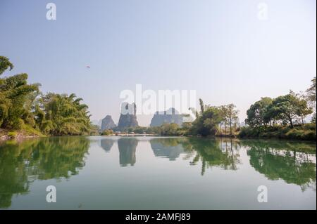 Lake with limestone karst hills foggy landscape reflecting in the river in Yangshuo, Guangxi province, China - Stock Photo