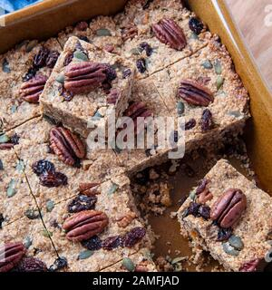 over head square shot  of cut  Plant based  vegan cake in a brown oven dish  ,recipe filled with nuts fruit and oats  copy space in background Stock Photo