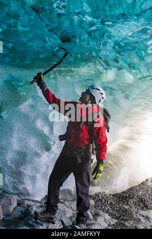 Ice climber in ice cave at Breidamerkurjokull Breiðamerkurjökull Ice Cave, Crystal Cave in Vatnajökull National Park, South East Iceland in January - Stock Photo
