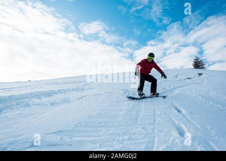 athletic snowboarder riding on slope in winter - Stock Photo