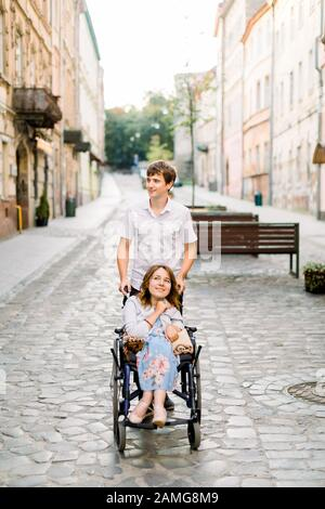 Happy smiling pretty woman in wheelchair and young handsome man at the old city center on sunny day - Stock Photo