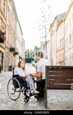 handsome man and pretty woman in wheelchair looking at each other on street. Lovely couple in wheechair walking together in the city - Stock Photo
