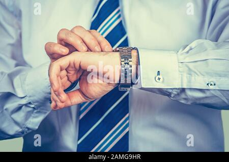 Closeup of businessman hand with watch on it while checking the time isolated on light green-yellow background. Torso and arms in elegant modern butto - Stock Photo