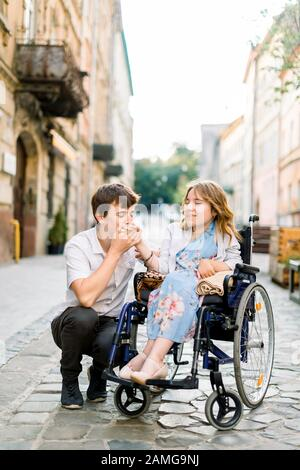 Young lovely Couple In Wheelchair, Enjoying A Day In The City, handsome man holding and kissing the hand of pretty young woman in wheelchair