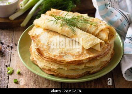Potato pancakes, not sweet, served with garlic cream sauce on rustic wooden table. - Stock Photo