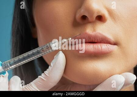 Close up of cosmetic botox injection in female lips. Front view of cosmetologist using syringe with special liquid and holding patients chin, isolated on blue. Concept of cosmetology, beauty. - Stock Photo