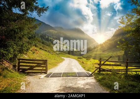 Open gate revealing view over winding hiking path into mountain area. Beautiful scenery with sunrise and dramatic sky. Zillertal, Austria. - Stock Photo