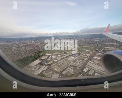 Wide angle view out window of Southwest Airlines aircraft, with wingtip visible, flying over Oakland, California, January 8, 2020. () - Stock Photo