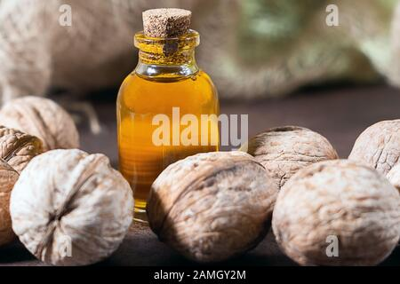Walnut oil in glass of bottle, on wooden background. healthy food for brain. Fresh walnuts background nut concept - Stock Photo