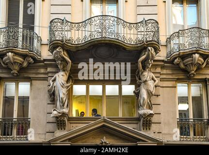 Baroque style façade of a palace decorated with a couple of caryatids supporting a balcony in Via Garibaldi in the centre of Turin, Piedmont, Italy - Stock Photo