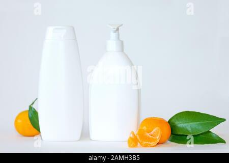 flat lay tangerine and mock up white plastic bottle on a white background - Stock Photo
