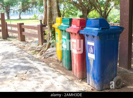 Trash can color yellow, green, red, blue on the side of the road. - Stock Photo
