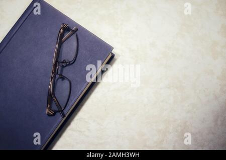 A blue hardcover book with a pair of reading glasses on top with copy space - Stock Photo