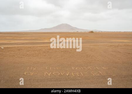 In The Middle of Nowhere written on the sand of Desert. Sal Island, Cape Verde. On background Pico do Fogo, Volcano. - Stock Photo