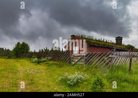 Typical Norwegian wooden red house in stormy cold weather along Peer Gynt Vegen in Western Norway near Gala - Stock Photo