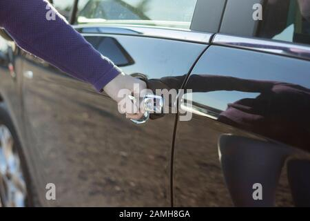 Hand on handle. Close-up of woman hand opening a car door. - Stock Photo