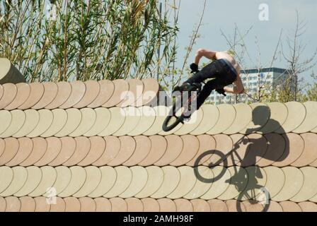 Unrecognizable BMX rider performing trick - Stock Photo