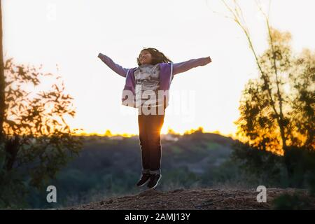 A young girl jumping with arms up on the top of a hill during a sunset. - Stock Photo
