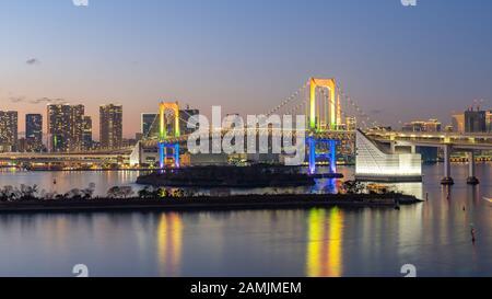 Tokyo city skyline at night with view of Rainbow bridge in Japan. Stock Photo