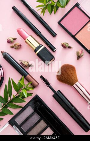 Make up natural cosmetics flat lay. Lipstick and nail polish, eye shadows and blush, brushes, pencils and rose buds against pink color background. - Stock Photo