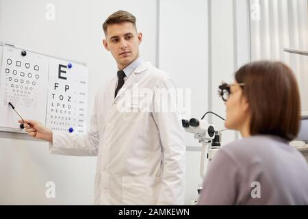 Portrait of young optometrist pointing at vision chart while checking eyesight of female patient in modern ophthalmology clinic - Stock Photo