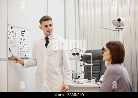 Portrait of young optometrist pointing at vision chart while checking eyesight of female patient in modern ophthalmology clinic, copy space - Stock Photo
