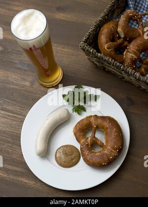 Bavarian snack with white sausage, parsley, pretzel, sweet mustard and a wheat beer. [automated translation] - Stock Photo