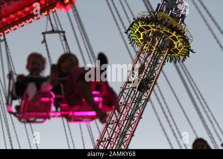 Passengers in the chain carousel at the evening Oktoberfest, in the background the ride Free Fall. [automated translation] - Stock Photo