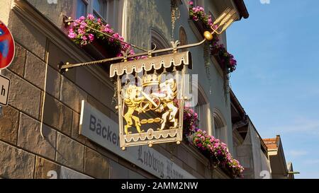 golden guild sign of a bakery in Bad Tölz, a crown, lions with crossed swords and a pretzel, and three rolls, balconies with flower boxes, 12.10...2014, [automated translation] - Stock Photo