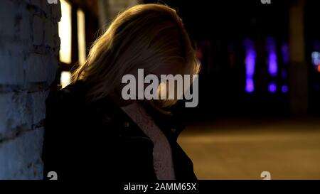 Drunk woman leaning on wall and feeling dizzy, hangover, unhealthy lifestyle - Stock Photo