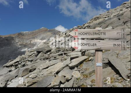 View from the Untere Weißzintscharte (2930m) to the Hochfeiler in the southern Zillertal Alps in South Tyrol. In the foreground, two signs point to the summit of the Hochfeiler and the Hochfeiler hut respectively. [automated translation] - Stock Photo