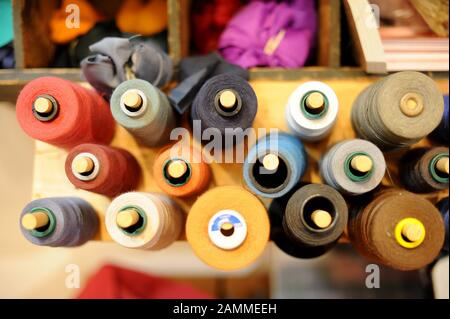 In the mobile repair workshop 'Worn Wear Mobil' of Patagonia in Munich's Leopoldstrasse you can repair your clothes. In the picture different coloured yarn rolls. [automated translation] - Stock Photo