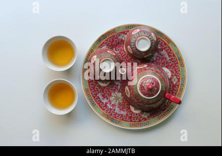 Vintage China porcelain tea set, teapot and two empty cups on saucer, the others filled with tea, the chinese characters mean longevity - Stock Photo