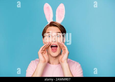 Closeup photo of amazing guy with funny bunny ears on head yelling novelty information spread gossips rumors people crowd wear casual pink t-shirt - Stock Photo