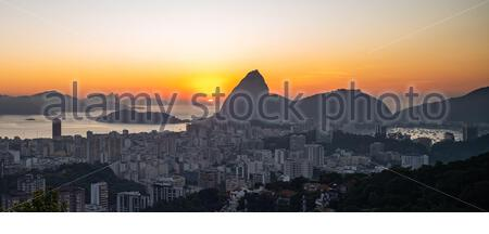 Panoramic view of the skyline of Sugarloaf Mountain and Botafogo in Rio de Janeiro, Brazil in the early morning at sunrise. Seen from Santa Teresa - Stock Photo