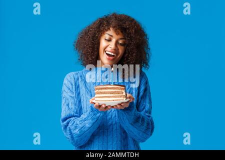 Celebration, holidays and party concept. Dreamy and lovely cute african-american woman with afro haircut, in sweater, tilt head and watching at lit - Stock Photo