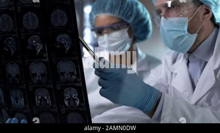 Neurosurgeon showing human MRI scan and giving explanation to medical intern - Stock Photo
