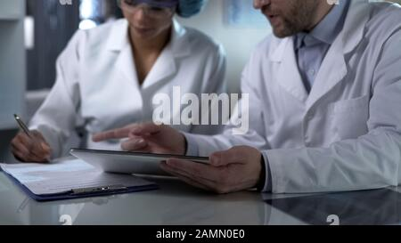 Male doctor holding tablet, giving female assistant instructions to note down - Stock Photo