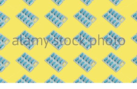 Seamless pattern of blister packs with blue pills inside on a yellow background - Stock Photo