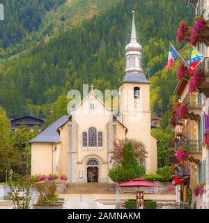 Chamonix Mont Blanc, France, street view with catholic church of St Michel in autumn, flowers and houses in town