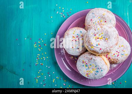 Carnival powdered sugar raised donuts - German Berliner donuts, Krapfen filled with jam - Stock Photo