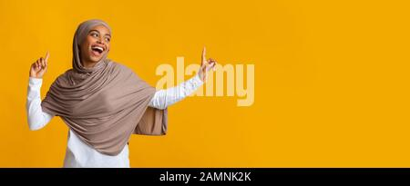 Carefree afro muslim girl in hijab looking aside at copy space - Stock Photo