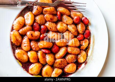 Closeup flat top view above of vibrant red wine sauce potato gluten free wheat gnocchi on white plate with lupine beans marinated in Italian Italy res - Stock Photo