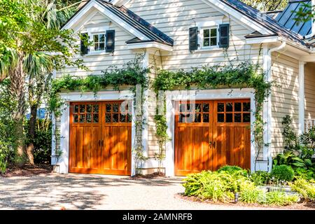 American residential house building in Charleston, South Carolina with two garage doors exterior with wooden architecture and ivy climbing plant - Stock Photo