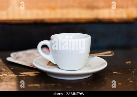 Macro closeup of espresso cappuccino coffee cup on plate saucer and background table in Italy cafe breakfast