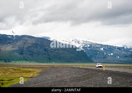Iceland mountains and car on ring road trip highway and snowcapped mountain cliff on cloudy day near Hof and Skaftafell national park