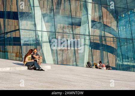 Norway, Oslo August 1, 2013: tourists and residents of the city relax lying and sitting on the parapet slabs in the area of the Opera house and the wa - Stock Photo
