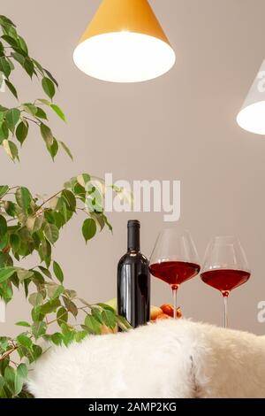 Dark bottle and two glasses of red wine on table in modern kitchen, lamps over table, green leaves of tree. Vertical. Copyspace. Place for text, lette - Stock Photo